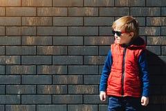 Modieus weinig jongen in een modern vest in zonnige dag, in openlucht op bakstenen muurachtergrond royalty-vrije stock afbeelding