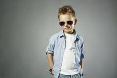 Modieus weinig jongen in zonnebril modieus jong geitje in jeans stock afbeelding