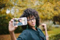 Modieus zwarte die selfie met smartphone in de herfst nemen royalty-vrije stock afbeeldingen