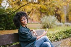 Modieus zwarte die selfie met smartphone in de herfstpark nemen stock afbeelding