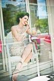 Modieuze aantrekkelijke jonge vrouw die een citroenplak in restaurant, voorbij de vensters proeven Het mooie Donkerbruine Stellen Stock Foto