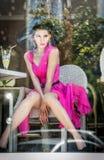 Modieuze aantrekkelijke jonge vrouw in roze kledingszitting in restaurant, voorbij het venster Het mooie vrouwelijke stellen in r Stock Afbeelding
