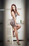 Modieuze aantrekkelijke jonge vrouw in vast korte kledingszitting op hoge barstoel Mooi roodharige op hoge hielen die op kruk ste stock foto's