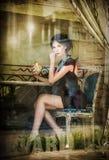 Modieuze aantrekkelijke jonge vrouw in zwarte kledingszitting in restaurant, voorbij het venster Het mooie donkerbruine stellen i Stock Foto