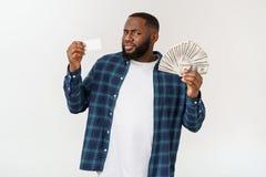 Modieuze Afrikaanse Amerikaan die in kostuum wit creditcard en geld in studio op witte achtergrond houden royalty-vrije stock afbeeldingen