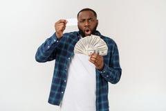 Modieuze Afrikaanse Amerikaan die in kostuum wit creditcard en geld in studio op witte achtergrond houden stock foto