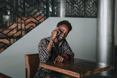 Modieuze Afrikaanse Amerikaanse jongen op het plaidoverhemd In die hipster en rapper bij straatzitting wordt gesteld op lijst hou royalty-vrije stock foto