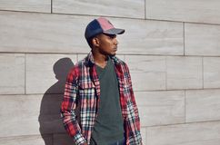 Modieuze Afrikaanse mens die rood plaidoverhemd, honkbal die GLB dragen, het jonge kerel stellen op stadsstraat, grijze bakstenen stock afbeelding
