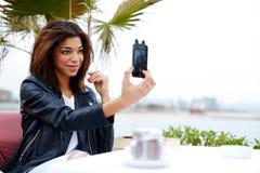 Modieuze afro Amerikaanse vrouw die zelfportret met smartphone nemen Stock Afbeelding