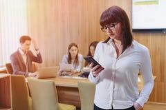 Modieuze beambtevrouw in glazen met telefoon in handen tegen achtergrond van werkende collega's stock afbeelding