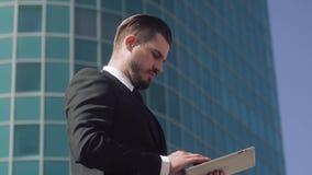 Modieuze bedrijfsmens die aan zijn tablet werken stock videobeelden