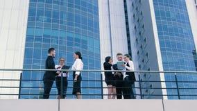 Modieuze bedrijfsmensen die over hun zaken voor de bureaubouw spreken stock video