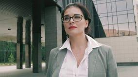 Modieuze bedrijfsvrouw die langs commercieel centrum lopen stock footage