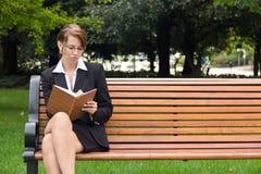 Modieuze bedrijfsvrouw die op parkbank situeren die in notitieboekje schrijven Royalty-vrije Stock Fotografie
