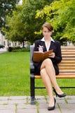 Modieuze bedrijfsvrouw die op parkbank situeren die in notitieboekje schrijven Stock Afbeelding