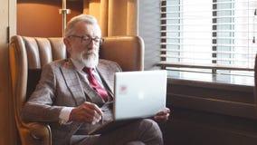 Modieuze bejaarde mannelijke schrijver die elegante kleren dragen die aan laptop werken stock video
