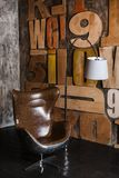 Modieuze binnenlands in zolderstijl grijs geweven pleister op de muur houten brieven comfortabele die leunstoel van bruin leer wo royalty-vrije stock foto