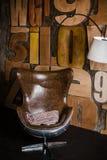 Modieuze binnenlands in zolderstijl grijs geweven pleister op de muur houten brieven comfortabele die leunstoel van bruin leer wo stock foto's