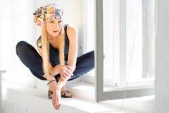 Modieuze blonde bij het geopende venster Stock Afbeelding