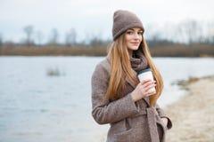 Modieuze blondevrouw in in stedelijk outwear stellend koud weer op de rivierbank Uitstekende filterfilm verzadigde kleur Dalingss stock foto