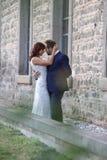 Modieuze bruid en bruidegom bij een park op hun huwelijksdag Mooi liefdeverhaal in aard, paar in liefde stock foto