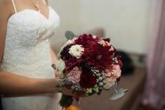 Modieuze bruid in het uitstekende witte kleding stellen met huwelijksboeket Royalty-vrije Stock Foto's
