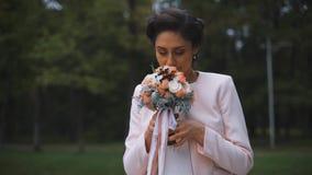 Modieuze bruid met een mooi boeket van bloemen in het park stock video