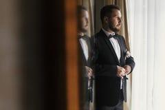 Modieuze bruidegom die op kostuum en vlinderdas bij vensterlicht zetten Confi stock fotografie