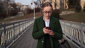 Modieuze busineswoman bezig met mobiele telefoon stock footage