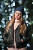 Modieuze dame die GLB en zwart jasje openlucht in Kerstmislandschap dragen met blauwe lichten op achtergrond. Portret van jonge vr royalty-vrije stock fotografie