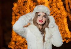 Modieuze dame die witte bonttoebehoren openlucht met heldere Kerstmislichten dragen op achtergrond. Portret van jonge mooie vrouw Stock Fotografie