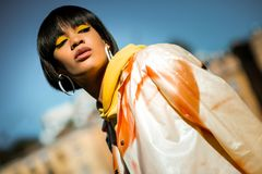 Modieuze donkerbruine dame die in al oranje kostuum fotograferen royalty-vrije stock afbeeldingen