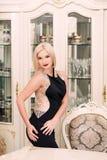 Modieuze elegante blondevrouw in schoonheids rijk binnenland, die zwarte kleding dragen stock foto's