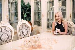 Modieuze elegante blondevrouw in schoonheids rijk binnenland, die zwarte kleding dragen stock foto