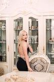 Modieuze elegante blondevrouw in schoonheids rijk binnenland, die zwarte kleding dragen royalty-vrije stock foto's