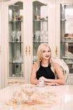 Modieuze elegante blondevrouw in schoonheids rijk binnenland, die zwarte kleding dragen royalty-vrije stock afbeeldingen