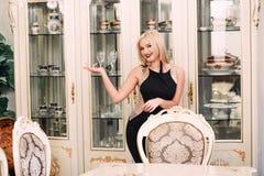 Modieuze elegante blondevrouw in schoonheids rijk binnenland, die zwarte kleding dragen stock afbeelding