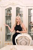 Modieuze elegante blondevrouw in schoonheids rijk binnenland, die zwarte kleding dragen royalty-vrije stock foto