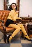Modieuze elegante donkerbruine vrouw in schoonheids rijk binnenland, die zwarte kleding dragen royalty-vrije stock foto