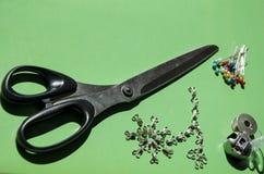Modieuze elementen: de metaalhaak en de sluitende ogen, de schaar, de spoelen en een wartel haken op een groene achtergrond vast stock foto's