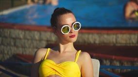 Modieuze en jonge vrouw in zonnebril die in de zonneschijnzomer zonnebaden stock videobeelden