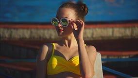 Modieuze en jonge vrouw in zonnebril die in de zonneschijnzomer zonnebaden stock footage