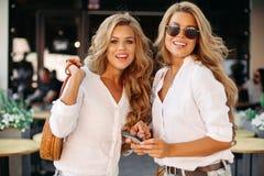 Modieuze en mooie winsten die smartphone gebruiken die bij camera glimlachen stock foto's