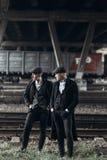 Modieuze gangstersmensen, die op achtergrond van spoorweg stellen engeland stock afbeelding