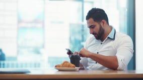 Modieuze gebaarde mens het drinken koffie, en het glijden van het scherm van de telefoon Het moderne leven, mededeling everyday stock videobeelden