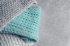 Modieuze gebreide pastelkleur gekleurde die sweaters op fluweelachtige stof worden opgestapeld De winter en lentetijdbreigoedkled stock fotografie