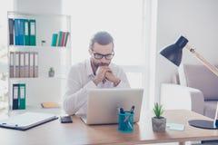 Modieuze geconcentreerde zakenman in de witte overhemdswerken in bureau stock afbeeldingen