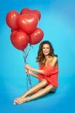 Modieuze, glimlachende, mooie vrouw met ballons over blauwe achtergrond Royalty-vrije Stock Afbeeldingen