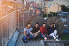 Modieuze groep vrienden die terwijl het zitten op een dak met avondstad met lichtenmachines op achtergrond stellen, Stock Foto