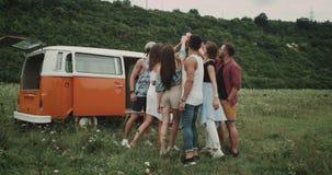 Modieuze groep vrienden gelukkige toejuichingen met elkaar bij de picknick in het midden van aard, erachter van hun retro bestelw stock footage